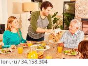 Glückliche Familie mit Großvater beim Abendessen oder Mittagessen zuhause. Стоковое фото, фотограф Zoonar.com/Robert Kneschke / age Fotostock / Фотобанк Лори