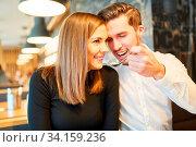 Junger Mann füttert seine Freundin beim Dating im Restaurant beim Abendessen. Стоковое фото, фотограф Zoonar.com/Robert Kneschke / age Fotostock / Фотобанк Лори