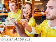 Freunde als Fans einer Mannschaft beim Feiern und Bier trinken in einem Pub. Стоковое фото, фотограф Zoonar.com/Robert Kneschke / age Fotostock / Фотобанк Лори