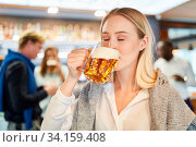 Junge Frau nimmt einen großen Schluck Bier am Feierabend in der Kneipe. Стоковое фото, фотограф Zoonar.com/Robert Kneschke / age Fotostock / Фотобанк Лори