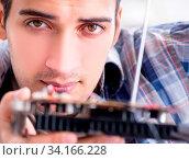 Professional repairman repairing computer in workshop. Стоковое фото, фотограф Zoonar.com/Elnur Amikishiyev / easy Fotostock / Фотобанк Лори