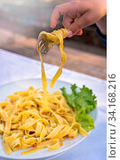 Child wrapping tagliatelle pasta with fork during lunch. Стоковое фото, фотограф Zoonar.com/Pawel Opaska / easy Fotostock / Фотобанк Лори