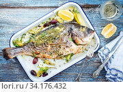 Fresh Greek barbecue gilthead seabream with peperoni and Kalamata olives as top view in a white skillet. Стоковое фото, фотограф Zoonar.com/H.LEITNER / easy Fotostock / Фотобанк Лори