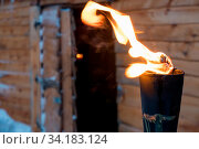 Fire burning inside metal torch in front of a wooden shed in a Sami people village, northern Norway. Стоковое фото, фотограф Zoonar.com/Pawel Opaska / easy Fotostock / Фотобанк Лори