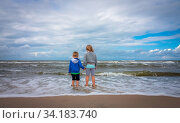Little boy and girl standing in the sea waters on the beach in summer. Стоковое фото, фотограф Zoonar.com/Pawel Opaska / easy Fotostock / Фотобанк Лори