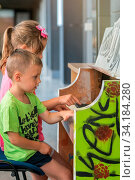 Little young caucasian siblings playing together on the piano outside train station. Стоковое фото, фотограф Zoonar.com/Pawel Opaska / easy Fotostock / Фотобанк Лори