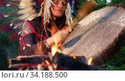 Shaman woman  in native American Indian headdress playing shaman frame drum at night in the forest. Стоковое видео, видеограф Алексей Кузнецов / Фотобанк Лори