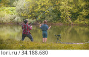 Two brothers on fishing - man pulling the rod and his little brother jumping beside him. Стоковое видео, видеограф Константин Шишкин / Фотобанк Лори