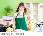 Купить «Neck injured young woman doing ironing at home», фото № 34189204, снято 29 мая 2018 г. (c) Elnur / Фотобанк Лори