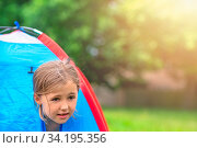 A young girl peering through an opening in a tent on a camping ground in summer. Стоковое фото, фотограф Zoonar.com/Pawel Opaska / easy Fotostock / Фотобанк Лори