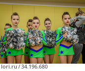 Moscow, Russia - December 22, 2019: Teenage girls, athletes in bright green leotards, with pom-pons waiting start show. Редакционное фото, фотограф Андрей Копылов / Фотобанк Лори