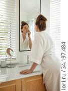 Купить «Woman touching her face while looking in the mirror», фото № 34197484, снято 17 октября 2019 г. (c) Wavebreak Media / Фотобанк Лори
