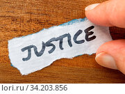 The word Justice concept and theme written on old paper on a grunge background. Стоковое фото, фотограф Zoonar.com/Morad HEGUI / easy Fotostock / Фотобанк Лори