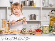 Купить «Smiling girl is demonstraiting vegetables dish in the kitchen», фото № 34206124, снято 27 января 2018 г. (c) Яков Филимонов / Фотобанк Лори