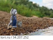 Игрушки. Вязаный крючком кот стоит с удочкой и ведром на берегу реки. Стоковое фото, фотограф Dmitry29 / Фотобанк Лори