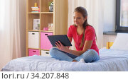 Купить «smiling girl with tablet pc sitting on bed at home», видеоролик № 34207848, снято 14 июня 2020 г. (c) Syda Productions / Фотобанк Лори