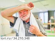 Senior Mann mit Schweiß auf der Stirn in einer Pause beim Sport Training im Fitnesscenter. Стоковое фото, фотограф Zoonar.com/Robert Kneschke / age Fotostock / Фотобанк Лори