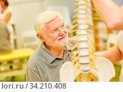Senior Mann in einer Rückenschule in der Physiotherapie mit einem Wirbelsäule Modell. Стоковое фото, фотограф Zoonar.com/Robert Kneschke / age Fotostock / Фотобанк Лори