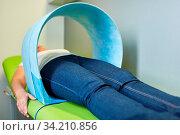 Patientin bekommt Magnetfeldtherapie als Naturheilkunde Verfahren beim Heilpraktiker. Стоковое фото, фотограф Zoonar.com/Robert Kneschke / age Fotostock / Фотобанк Лори
