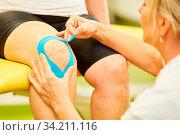 Heilpraktikerin befestigt ein Kinesio Tape am Knie eines Patienten in der Physiotherapie. Стоковое фото, фотограф Zoonar.com/Robert Kneschke / age Fotostock / Фотобанк Лори