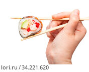 Female hand with disposable chopsticks holds western-style sushi roll close up isolated on white background. Стоковое фото, фотограф Zoonar.com/Valery Voennyy / easy Fotostock / Фотобанк Лори