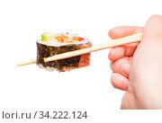 Female hand with disposable chopsticks holds western-style sushi roll isolated on white background. Стоковое фото, фотограф Zoonar.com/Valery Voennyy / easy Fotostock / Фотобанк Лори