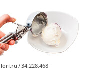 Disher scoop puts a ball of ice cream in bowl isolated on white backgrouns. Стоковое фото, фотограф Zoonar.com/Valery Voennyy / easy Fotostock / Фотобанк Лори