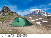 Green tourist tent Red Fox for travel and camping standing in mountain on background of volcanic landscape, blue sky with clouds (2015 год). Редакционное фото, фотограф А. А. Пирагис / Фотобанк Лори
