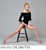 Beautiful blonde gymnast woman in black costume. She is sitting on high chair in Studio with grey background. Стоковое фото, фотограф Zoonar.com/© Dmitry Raikin / easy Fotostock / Фотобанк Лори