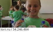 Girl wearing recycle symbol tshirt holding plastic bottles. Стоковое видео, агентство Wavebreak Media / Фотобанк Лори
