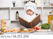 Girl is looking recipe in culinary book in the kitchen. Стоковое фото, фотограф Яков Филимонов / Фотобанк Лори
