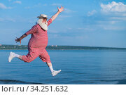 An elderly man in a striped retro swimsuit runs and jumps along the beach. A cheerful gray-haired old man with a beard in a hat is resting at the sea. Стоковое фото, фотограф Михаил Решетников / Фотобанк Лори