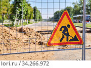 Road sign Roadworks ahead on the fence against the background of a blurred dug street. Стоковое фото, фотограф Евгений Харитонов / Фотобанк Лори