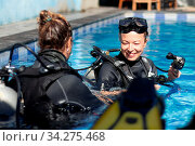 Female diving instructor teaches student to scuba dive in swimming pool. Lady getting first experience with scuba diving under the guidance of experienced recreational diving instructor on vacation. Стоковое фото, фотограф Zoonar.com/Matej Kastelic / easy Fotostock / Фотобанк Лори