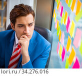 Young handsome employee with many conflicting priorities. Стоковое фото, фотограф Elnur / Фотобанк Лори