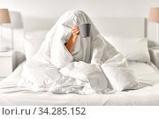 woman with coffee sitting under blanket in bed. Стоковое фото, фотограф Syda Productions / Фотобанк Лори