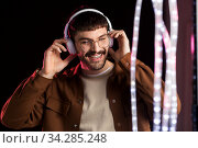 man in headphones over neon lights of night club. Стоковое фото, фотограф Syda Productions / Фотобанк Лори