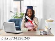 graduate student with laptop and diploma at home. Стоковое фото, фотограф Syda Productions / Фотобанк Лори