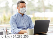 man in mask with laptop working at home office. Стоковое фото, фотограф Syda Productions / Фотобанк Лори