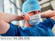 Chirurg in blauer OP-Kleidung mit Mundschutz und Haube vorbereitet für den Notdienst. Стоковое фото, фотограф Zoonar.com/Robert Kneschke / age Fotostock / Фотобанк Лори