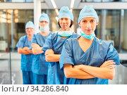 Junge Chirurgin mit verschränkten Armen vor ihrem Chirurgie und Notfall Team. Стоковое фото, фотограф Zoonar.com/Robert Kneschke / age Fotostock / Фотобанк Лори