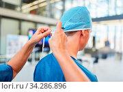 Arzt in der Notaufnahme oder Intensivstation mit blauer Haube und OP-Kleidung. Стоковое фото, фотограф Zoonar.com/Robert Kneschke / age Fotostock / Фотобанк Лори