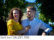A date between a young girl and a guy on a Sunny summer day. Young beautiful couple on walk in the city. Man and woman at a love meeting with hugs and kisses outdoors. Стоковое фото, фотограф Кривошеина Елена Леонидовна / Фотобанк Лори