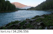 Video of Sunrise over mountain Altai landscape with river Katun and boulders on foreground and forest on the far bank. Стоковое видео, видеограф Serg Zastavkin / Фотобанк Лори