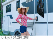 A beautiful red-haired woman in a hat stands at a white mobile home. A smiling girl in a striped jacket opens the door to the Caravan for life and family road trips. Редакционное фото, фотограф Михаил Решетников / Фотобанк Лори