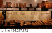 Baked baguettes on showcase in bakery shop. Inscriptions in catalan with the name baking. Стоковое видео, видеограф Яков Филимонов / Фотобанк Лори