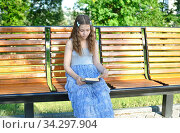 Smiling Girl reading a book while sitting on the bench. Стоковое фото, фотограф Бражников Андрей / Фотобанк Лори