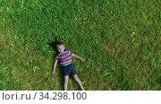 Ыеселый мальчик лежит на зеленой траве. Вид сверху. Стоковое видео, видеограф Beerkoff / Фотобанк Лори