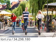 Trendy fashinable group of friends riding public rental electric scooters in urban city environment. New eco-friendly modern public city transport in Ljubljana, Slovenia. Стоковое фото, фотограф Matej Kastelic / Фотобанк Лори