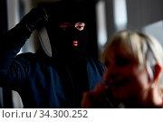Räuber bedroht Frau zu Hause mit einem großen Messer. Стоковое фото, фотограф Zoonar.com/Robert Kneschke / age Fotostock / Фотобанк Лори
